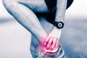 47866084-足首の足の痛み、痛みや痛みを伴う足の筋肉、捻挫やけいれん痛み赤ピンクの明るい場所でいっぱいを抱きかかえた。トレーニング運動や屋外を実